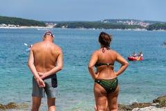 Tourists on Kamenjak peninsula beach by the Adriatic Sea in Premantura, Croatia. PREMANTURA, CROATIA - JULY 28: Tourists on Kamenjak peninsula beach by the stock image