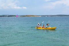 Tourists sailing on kayak on Kamenjak peninsula in Premantura, Croatia. PREMANTURA, CROATIA - JULY 28: Tourists sailing on kayak on Kamenjak peninsula by the stock photo