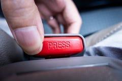 Premendo e liberando la cintura di sicurezza inarchi in automobile Fotografia Stock