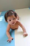Première fois de essai d'ascension de rampement de bébé garçon adorable Images stock