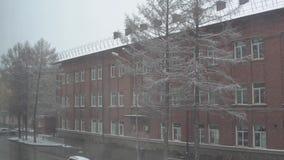 Première neige sur le fond du vieil immeuble de brique le jour d'hiver banque de vidéos