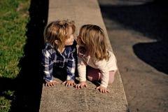 Première passion puérile Baiser de garçon et de fille sur le bord en pierre le jour ensoleillé Photo libre de droits