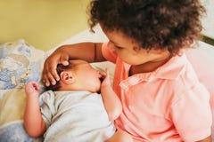 Première rencontre de garçon africain adorable d'enfant en bas âge et de son frère nouveau-né Photographie stock libre de droits