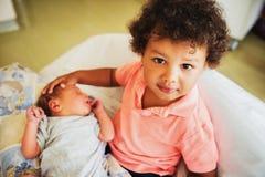 Première rencontre de garçon africain adorable d'enfant en bas âge et de son frère nouveau-né Photos libres de droits