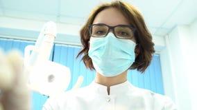 Première vue de personne d'un jeune dentiste féminin dans des approches de masque avec des outils medias Jeune position de doct banque de vidéos