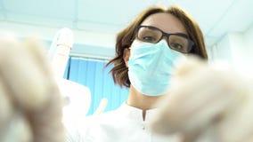 Première vue de personne d'un jeune dentiste féminin dans des approches de masque avec des outils medias Jeune position de doct clips vidéos
