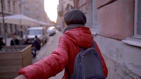 Première vue de personne de la jeune femme dans la veste rouge et le chapeau gris marchant sur la rue banque de vidéos