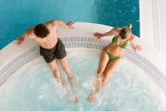 Première vue - les jeunes couples détendent dans la piscine Photos stock