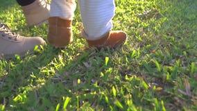 Premières étapes de marche de bébé garçon avec la maman dehors banque de vidéos