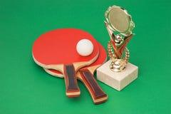 Premi di sport e racchette di tennis sulla tabella verde fotografia stock