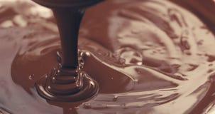 Premie donkere gesmolten chocolade die van gestemde lepelclose-up worden gegoten Stock Afbeeldingen
