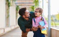 Premier jour à l'école le père mène la fille d'école de petit enfant dans f photo libre de droits