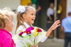 Premier-niveleuse à l'école d'abord de septembre dans la salutation ondulant son amie Photo libre de droits