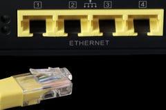 Premier plan d'un câble jaune de réseau et de quatre ports de réseau à t Photo stock
