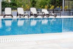 Premier plan de piscine avec des chaises de plate-forme placées par dans la rangée avec la réflexion à l'eau et à l'arrière-plan  photos libres de droits