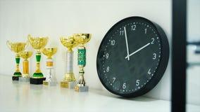 Premio del trofeo per la manifestazione del vincitore sullo scaffale azione Orologio e trofei sullo scaffale Il concetto di tempo Fotografia Stock