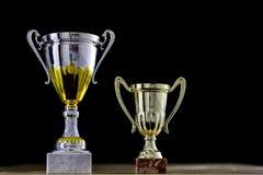 Premio, una tazza che sta sulla tavola Premio della tazza su un backgro nero fotografia stock libera da diritti