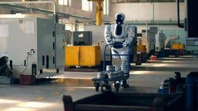 Premisas de fábrica con un cyborg que empuja una carretilla adelante almacen de video