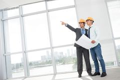 Premises. Tilted image of two supervisors comparing blueprint with actual building interior stock image