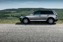 Premium car stay on asphalt road near mountain at daytime. Premium grey car stay on asphalt road near mountain at daytime Royalty Free Stock Images