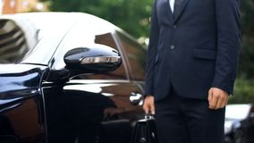Premium class driver standing near luxury car, work for refugees, service. Stock photo royalty free stock photos