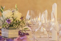 Premium dinner gala table with glasses napkins and flowers. High class arrangement for e.g. a wedding, birthday or business meeting Royalty Free Stock Images