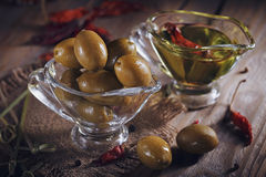 Premium extra virgin olive oil and green olives with fresh herbs Royalty Free Stock Photos