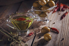 Premium extra virgin olive oil and green olives with fresh herbs Royalty Free Stock Photo
