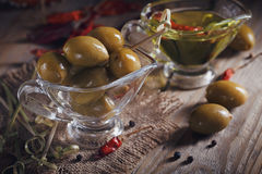 Premium extra virgin olive oil and green olives with fresh herbs Stock Image