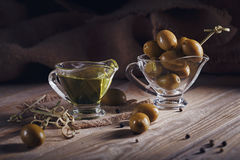 Premium extra virgin olive oil and green olives with fresh herbs Stock Photos