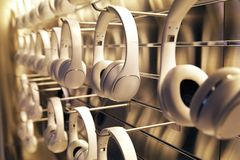 Premium Headphones on the Rack. Premium generic white headphones stacked on a wall rack for sales in a store stock photo