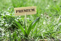 Premium wooden sign. Premium on wooden sign in garden with white spring flower royalty free stock images