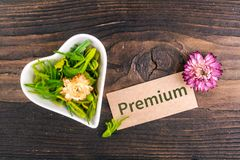 Premium word on card. With dried flower and heart shape bowl on wood royalty free stock photo