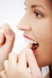 Prenant soin des dents avec un filé dentaire. Photographie stock