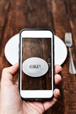 Prenant une photo d'un plat avec le mot affamé Photographie stock libre de droits