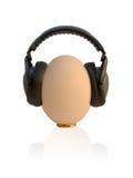 Prenatal Entertainment. Sweaty egg with headphones on Stock Photos