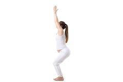 Prenatal Yoga, Utkatasana. Full length portrait of young pregnant fitness model in white sportswear doing yoga or pilates training, Utkatasana, Chair Pose, white Royalty Free Stock Photography