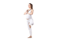Prenatal Yoga, Vrikshasana pose. Full length portrait of young pregnant fitness model in white sportswear doing yoga or pilates training, Vrikshasana, Tree Pose Royalty Free Stock Photography