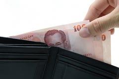 Prenda i soldi dal raccoglitore Fotografia Stock Libera da Diritti