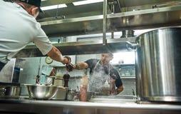 Prenda l'IT Giovane cuoco unico professionista in grembiule che dà una smerigliatrice di pepe al suo assistente mentre processo d fotografia stock