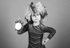 Prenda la cura del vostro tempo Bambino allegro sveglio della ragazza indossare la parrucca riccia dell'arcobaleno La vita ? dive fotografia stock