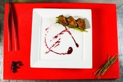 prendedero ahumado de la pechuga de pato en la placa blanca en el tablero culinario rojo Imágenes de archivo libres de regalías