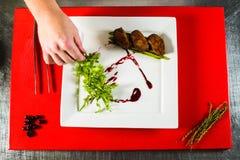 prendedero ahumado de la pechuga de pato en la placa blanca en el tablero culinario rojo Imagenes de archivo
