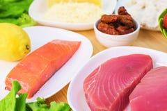 Prendedero apetitoso crudo del atún en una tabla con una yarda de ensalada griega con los salmones y pepinos y tomates del limón  Imágenes de archivo libres de regalías