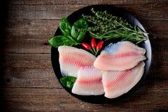Prendedero crudo fresco de los pescados de la Tilapia con pimienta del tomillo, del romero, de la albahaca y de chile fotografía de archivo