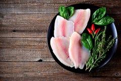 Prendedero crudo fresco de los pescados de la Tilapia con pimienta del tomillo, del romero, de la albahaca y de chile fotos de archivo libres de regalías