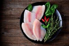 Prendedero crudo fresco de los pescados de la Tilapia con pimienta del tomillo, del romero, de la albahaca y de chile foto de archivo libre de regalías