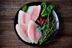 Prendedero crudo fresco de los pescados de la Tilapia con pimienta del tomillo, del romero, de la albahaca y de chile imagen de archivo libre de regalías