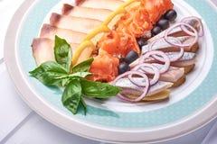 Prendedero de arenques con los salmones y las cebollas en la superficie de madera blanca imagen de archivo