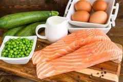 Prendedero de color salmón crudo con las verduras en tabla de cortar de madera Ingredientes para los clafoutis fotografía de archivo libre de regalías